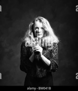 Eine junge Frau vor der Kamera hält eine Pistole - Stockfoto