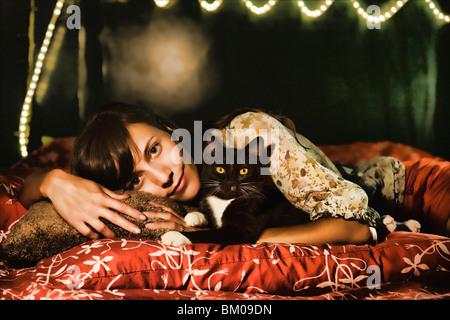 Hübsche junge Frau mit ihrer Katze auf einem Bett mit roten Seidenkissen - Stockfoto
