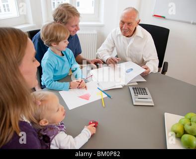 Berater, die Papiere mit einer Familie zu diskutieren - Stockfoto
