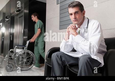 Arzt mit Pfleger mit einem Rollstuhl auf einem Stuhl sitzend - Stockfoto