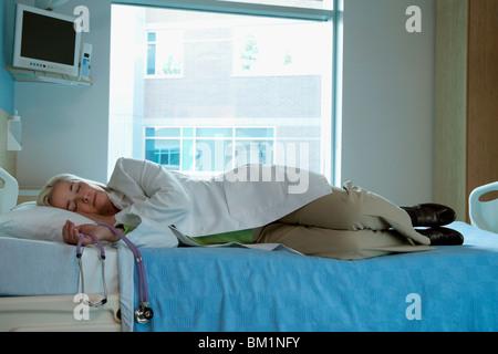 Ärztin, die am Bett des Patienten schlafen erschöpft
