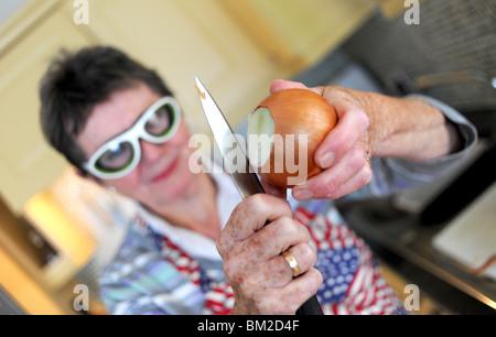 Frau vorbereiten und schälen Zwiebeln mit speziellen Brille Augen Gießen stoppen - Stockfoto