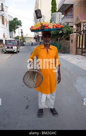Mann in gelb Kurta mit Tablett mit Snacks auf den Kopf und die Tabelle unter dem Arm, auf dem Markt zu verkaufen, - Stockfoto