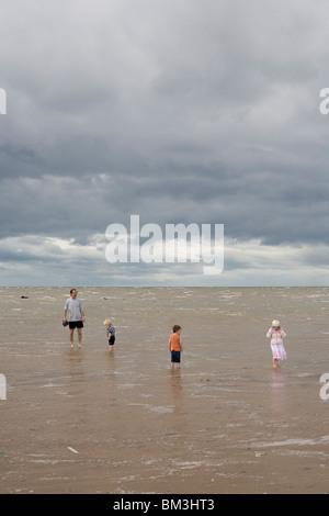 Kinder und Vater spielen im Meer mit einem Sturm kommen St Annes Lancashire UK - Stockfoto