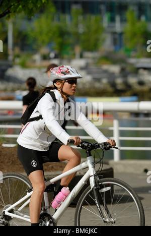 Seitenansicht einer erwachsenen Frau, die mit dem Fahrrad. - Stockfoto