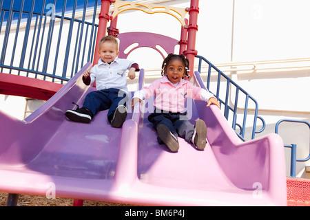 Fort Lauderdale, Florida, Vereinigte Staaten von Amerika; Zwei kleine Kinder, die hinunter der Rutsche auf dem Spielplatz - Stockfoto