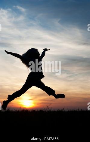 Young Girl energetisch Spaß herumspringen. Silhouette - Stockfoto