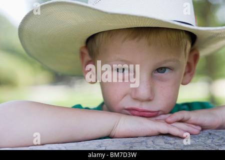 Ein kleiner Junge einen Cowboy-Hut mit einem verärgert Gesichtsausdruck - Stockfoto