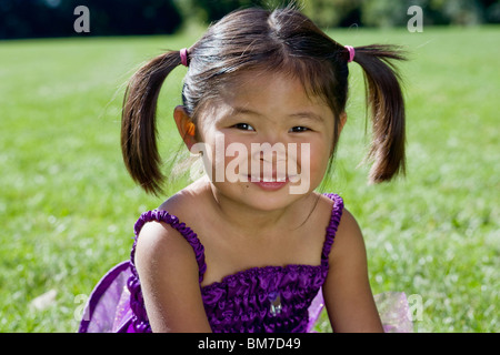 Ein junges Mädchen sitzt auf dem Rasen - Stockfoto