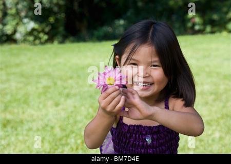 Ein junges Mädchen, die eine Blume - Stockfoto