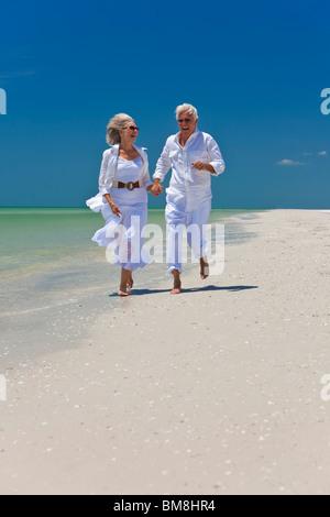 Glückliches Paar der senior Mann und Frau laufen, lachen und Hand in Hand auf einem einsamen tropischen Strand mit - Stockfoto