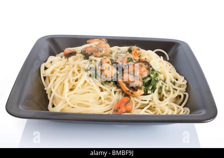 typisch italienische Küche: Spaghetti mit Muscheln und Knoblauch. Teller isoliert auf weißem Hintergrund mit Beschneidungspfad - Stockfoto