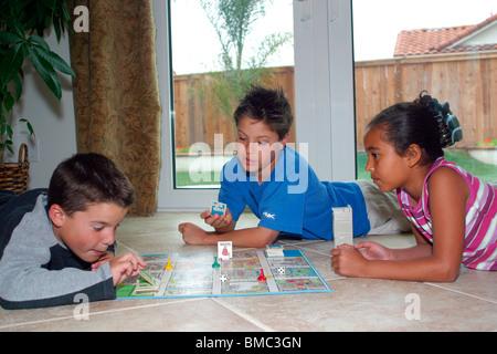 3 multi-ethnischen Kinder Brettspiel indoor innen auf Bodenniveau anzeigen USA Herr © Myrleen Pearson - Stockfoto