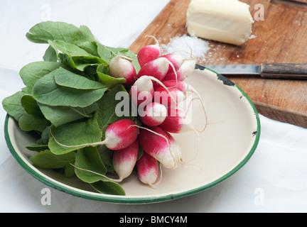 Frische Radieschen In eine Emaille-Schüssel, mit Butter, Salz und ein Messer im Hintergrund - Stockfoto
