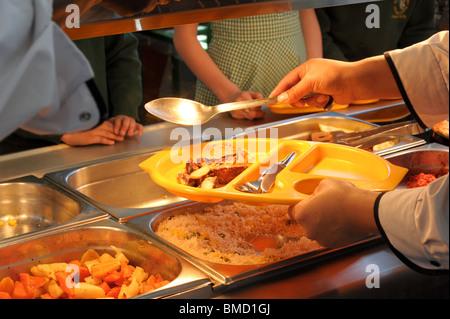eine abendessen dame serviert schule abendessen in einer kantine ber einer hei en platte mit. Black Bedroom Furniture Sets. Home Design Ideas