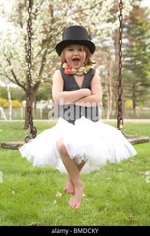 Kleines Mädchen im Zylinderhut auf Schaukel - Stockfoto