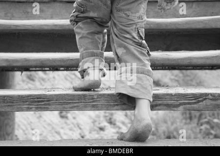 Junge mit sandigen Füßen Holztreppe hinauf - Stockfoto
