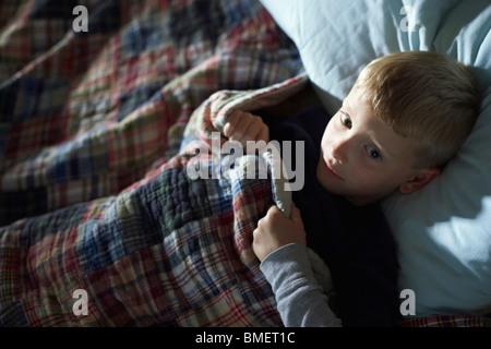 Ein Junge Verlegung wach im Bett - Stockfoto