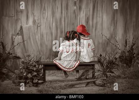 Ein Mädchen und ein Junge sitzt auf einer Bank tragen passende Baseball Uniformen - Stockfoto