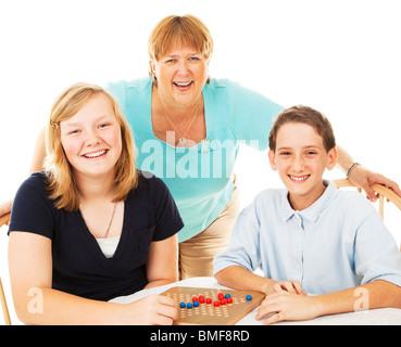 Mutter und zwei Kinder haben Spaß Board Spiele zu spielen. Isoliert auf weiss.