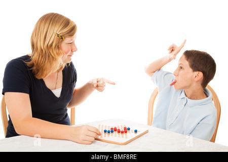 Kleiner Bruder Schwester teenage verrückt, während sie eine Brettspiel spielen. Isoliert auf weiss.