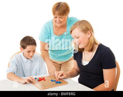 Mutter und zwei Kinder spielen Brettspiele. Isoliert auf weiss.