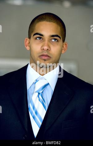 Städtischen Berufseinsteiger in seinem frühen 20 trägt einen dunklen Anzug. - Stockfoto