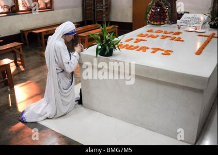 Indien Kalkutta Kalkutta, Nonne beten am Grab von Mutter Teresa an der Mutter Teresa Haus, mit Blumen Liebe geschrieben, - Stockfoto