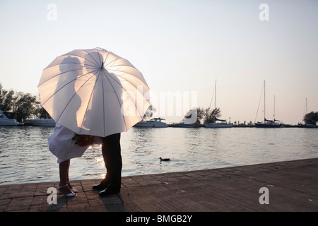 Silhouetten von Mann und Frau hinter einem Regenschirm - Stockfoto