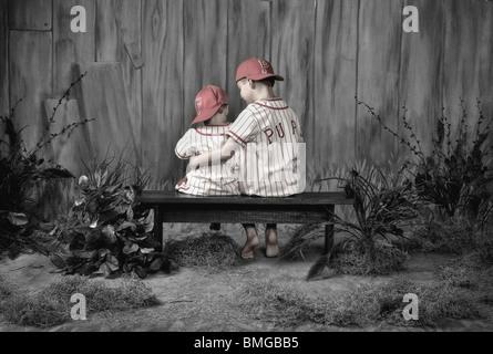 Zwei jungen tragen Baseball Uniformen und sitzen auf einer Bank zusammen - Stockfoto