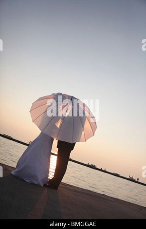 Silhouette der Braut und Bräutigam hinter einem Regenschirm - Stockfoto