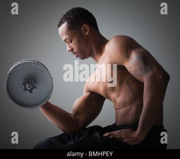 Muskulöser Mann eine Hantel heben - Stockfoto