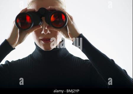 Frau, die durch ein Fernglas - Stockfoto