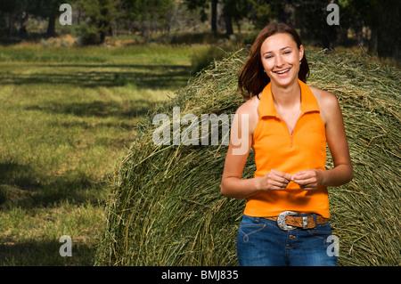 Lächelnde Teenager-Mädchen neben einem Heuballen außerhalb in einem Feld. - Stockfoto