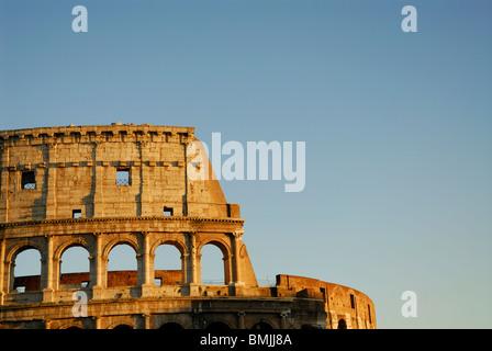 Der Roman Colosseum im goldenen Abendlicht einfachen blauen Himmel im Hintergrund. - Stockfoto