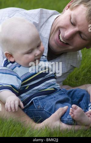 Nahaufnahme eines jungen Vater und Sohn draußen auf der Wiese - Stockfoto
