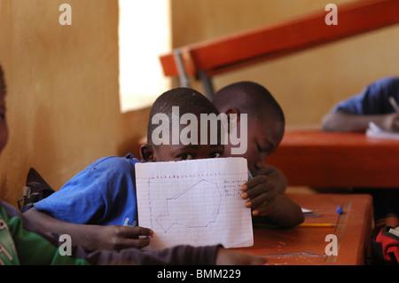 Niamey, Niger afrikanischen Schülern an ihren hölzernen Schreibtisch im Klassenzimmer sitzen.