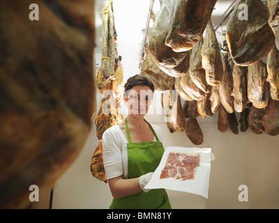 Frau mit frisch geschnittenen Schinken - Stockfoto