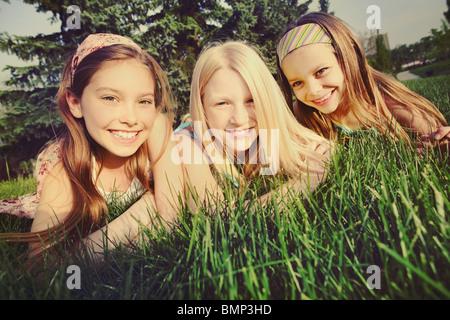 Edmonton, Alberta, Kanada; Drei Mädchen, die Verlegung auf dem Rasen - Stockfoto