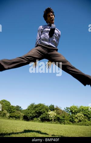 Der Mensch ist Business-Bekleidung springen in der Luft im Park - Stockfoto