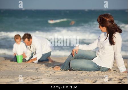 Fort Lauderdale, Florida, Vereinigte Staaten von Amerika; Vater und Sohn spielen im Sand am Strand während der Mutter - Stockfoto