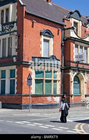 Junge Frau zu Fuß Vergangenheit mit Brettern vernagelt, geschlossen Pub (ehemals Langworthy Hotel), Langworthy Road, - Stockfoto