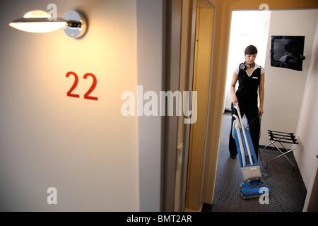 hotel zimmer service housekeeping die bei der arbeit in einem hotelzimmer aufr umen die. Black Bedroom Furniture Sets. Home Design Ideas