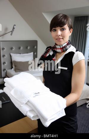 Hotel, Zimmer-Service, Housekeeping, die bei der Arbeit in einem Hotelzimmer. Aufräumen, die Betten machen. - Stockfoto