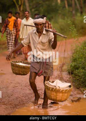 Kerala, Indien; Fischer tragen Körbe Schlamm Weg - Stockfoto