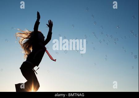 Young Girl energetisch Spaß springen und fangen Luftblasen bei Sonnenuntergang. Silhouette - Stockfoto