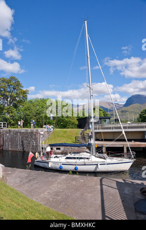 Eine Yacht ist der Caledonian Canal auf treppenartigen Fort William mit dem A830 Straße Drehbrücke geöffnet auf - Stockfoto