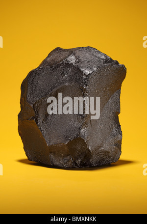 Ein großes Stück bituminöse Steinkohle auf einem leuchtend gelben Hintergrund - Stockfoto