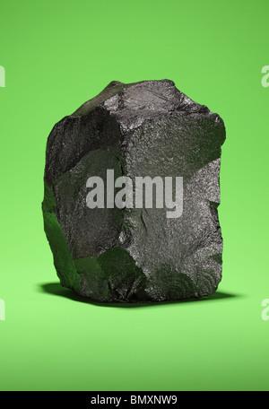 Ein großes Stück bituminöse Steinkohle auf einem hellen grünen Hintergrund - Stockfoto