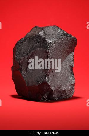 Ein großes Stück bituminöse Steinkohle auf einem leuchtend roten Hintergrund - Stockfoto